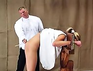 Dzejisis has been extra naughty and is placed in a guillotine to receive her caning. The headmaster lifts her dress and uses his cane to turn her bare